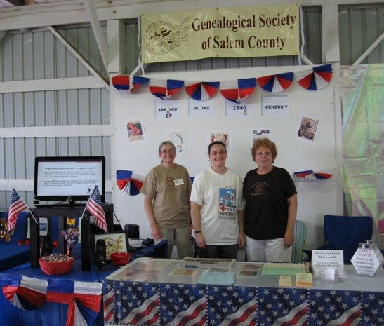 Three members pose at the Genealogical Society's 1940s Census themed booth