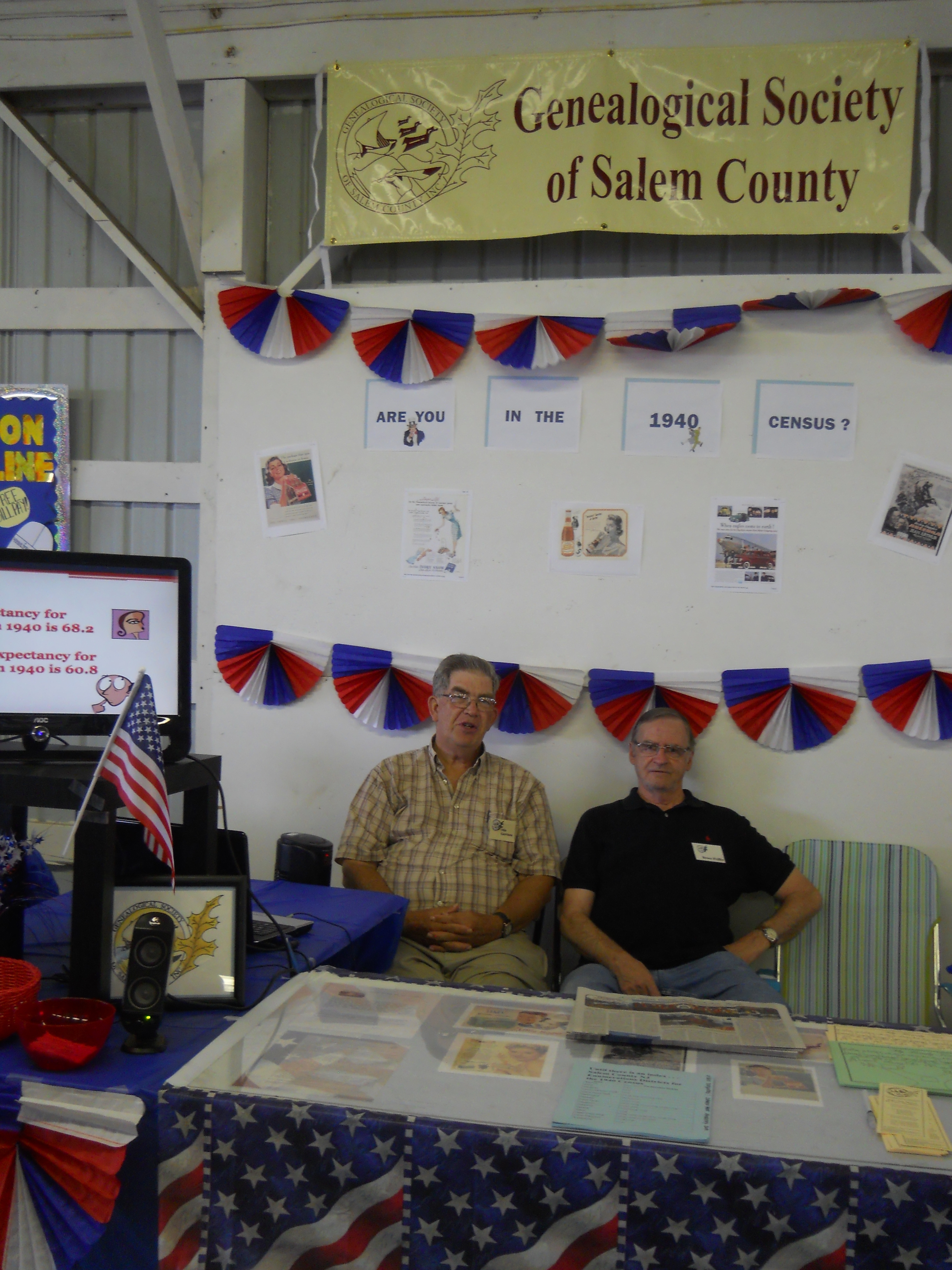 Two members pose at the Genealogical Society's 1940s Census themed booth
